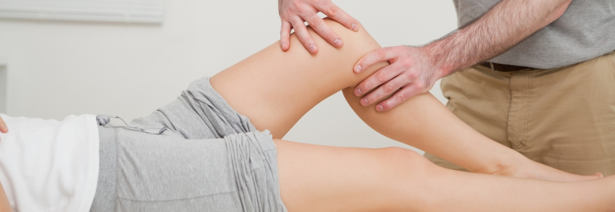 Physiotherapist working on client's knee